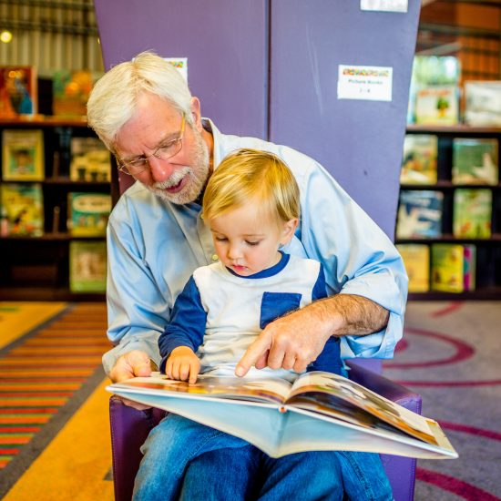 Grandfather Teaches Grandson to Read at Library